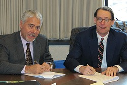 Jerry Jung (left) and Chris MacAllister sign the final documents for the Michigan CAT purchase.
