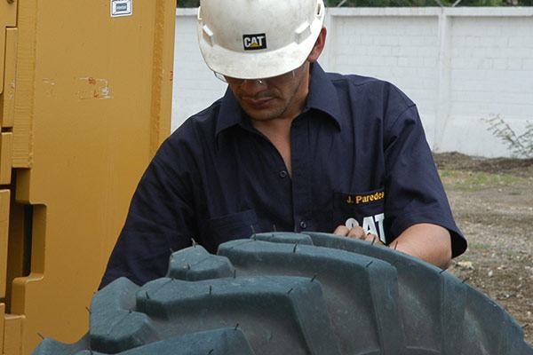 Worker with Cat shirt and construction helmet inspecting a large tire