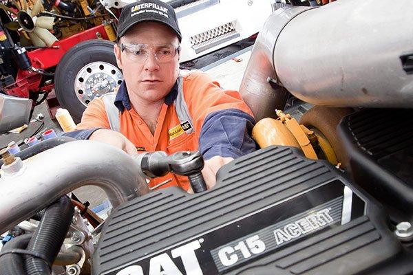 Cat mechanic working on an engine