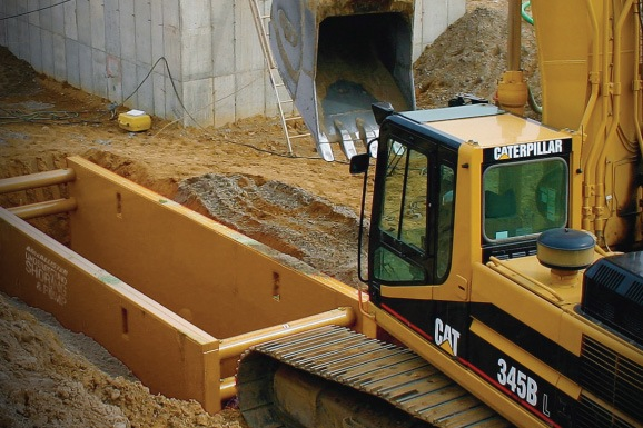 Cat excavator with shoring in the trench
